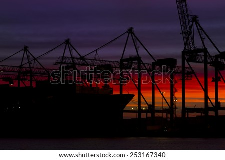 Huge container cargo  ship moored to a wharf at dusk - stock photo