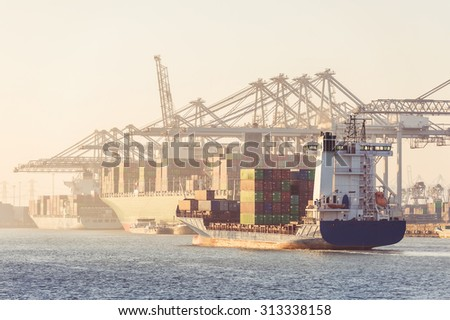 Huge container ship, coasters, supply vessels being loaded and unloaded by the huge overhead cranes of a busy transhipment harbor during a hazy afternoon - stock photo