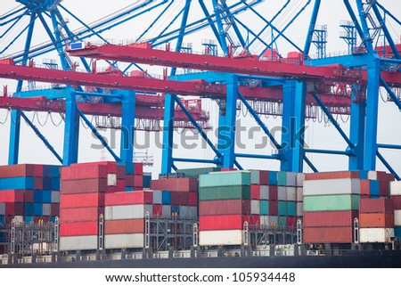 Huge container ship fully loaded in port terminal - stock photo