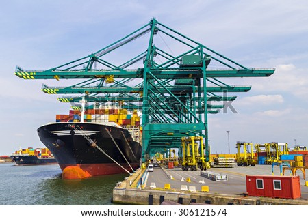 Huge container ships being loaded with cranes in Antwerp container terminal - stock photo