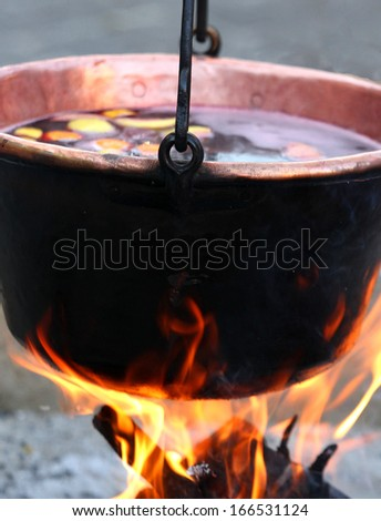 huge copper cauldron with the tasty mulled wine cooked over the open fire - stock photo