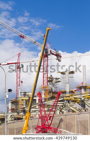 Huge crane and construction building. Big construction crane and the building against the sky background. Tower Crane in Construction site. - stock photo