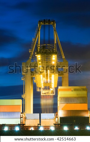 Huge crane unloading containers from a container ship at dusk - stock photo
