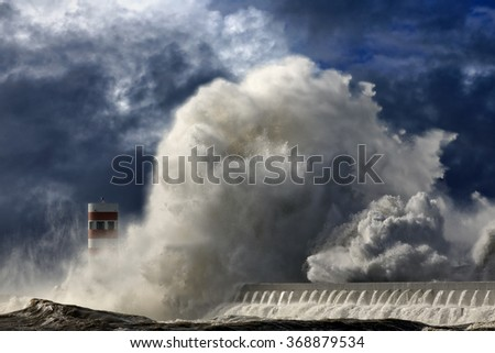 Huge dramatic sea wave over pier and lighthouse. Enhanced sky.