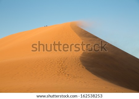 Huge dune in Nambi desert with tourists in a windy day