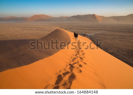 Huge dune in Nambi desert with tourists in a windy day - stock photo