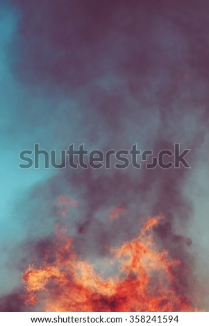 Huge flame against the blue sky during late day. Copyspace - stock photo