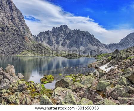 Huge fragments of rocks - granite, on the shore of a mountain lake. Tunka range. Siberian Alps. Eastern Siberia - stock photo