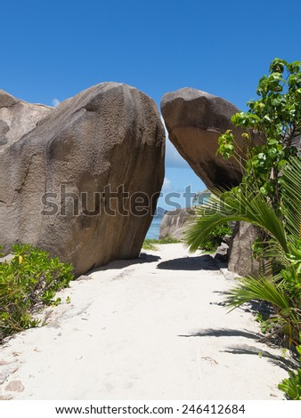 huge granite rocks and a path of white sand on the island of La Digue, Seychelles - stock photo
