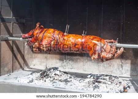 huge grilled pork fact, medieval fair in Spain - stock photo