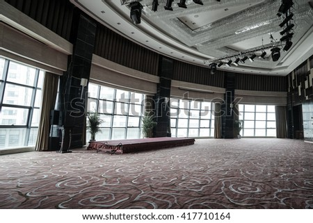 Huge Hall interior with red carpet and ceiling with lights as conference hall in luxury hotel.