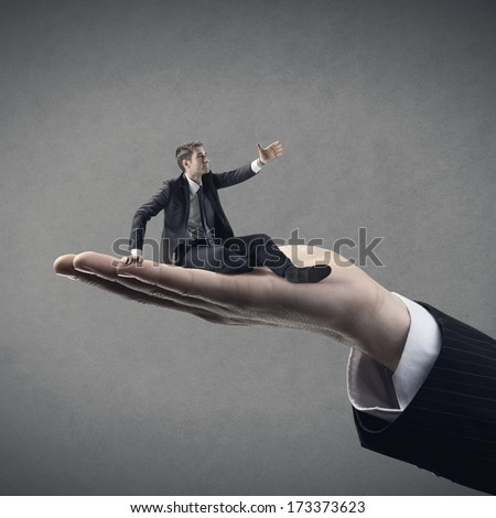 Huge hand helping young business on gray background.