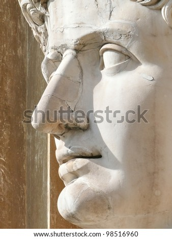 Huge head of a beautiful young man sculptured in stone. Ideal for love, romance, nostalgia, youth, plastic surgery design - stock photo