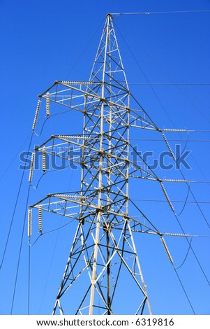 Huge high voltage electricity tower in the field.
