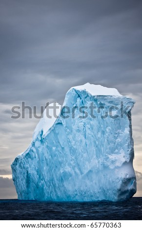 Huge iceberg in Antarctica, dark sky - stock photo