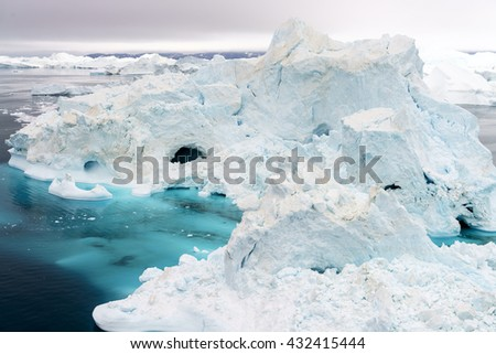 Huge Icebergs drifting in polar arctic icefjord at the west greenland coast in the early morning light. Ilulissat Icefjord, North West Coast, Greenland. - stock photo