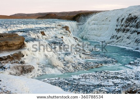 Huge Icelandic Gullfoss waterfall is covered by ice at winter.