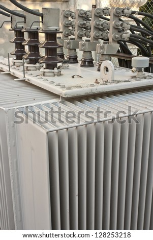 Huge industrial high-voltage substation power transformer at an power plant - stock photo