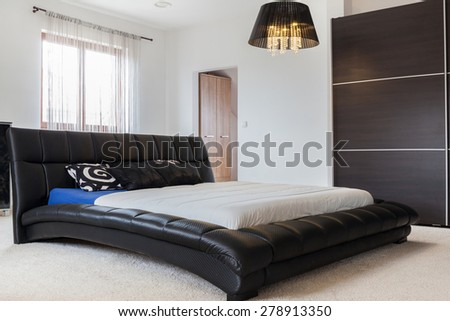 Huge leather bed in bedroom in the residence - stock photo