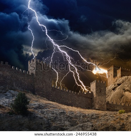 Huge lightning from dark stormy sky strikes old fortress - stock photo