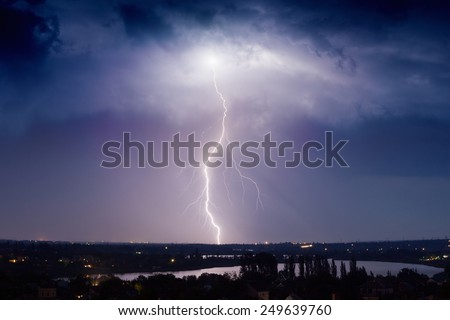 Huge lightning from dark stormy sky strikes small town - stock photo