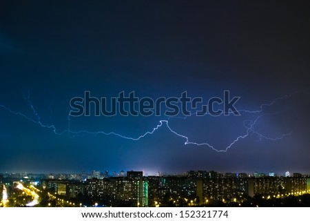 Huge Lightning on the horizon over the city at night with illuminated city - stock photo