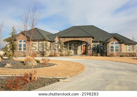 Huge modern one level house with long driveway and newspaper out front - stock photo