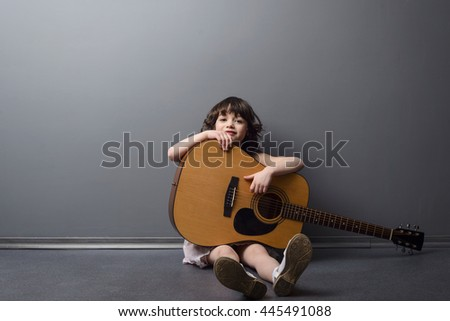 Huge musical instrument for a little girl holding it on the floor. Acoustic guitar in child's hands. Interest from a childhood for music. - stock photo