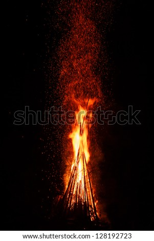 Huge night fire with sparks against a dark