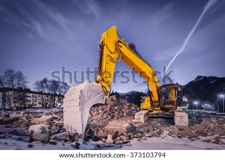 huge orange shovel digger on demolition site at night