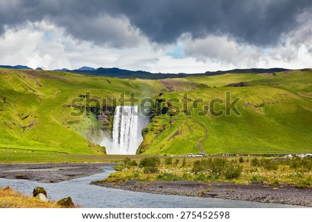Huge picturesque waterfall and creek running along the road. Iceland, waterfall Skogafoll - stock photo