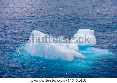 Huge piece of ice in the water - stock photo