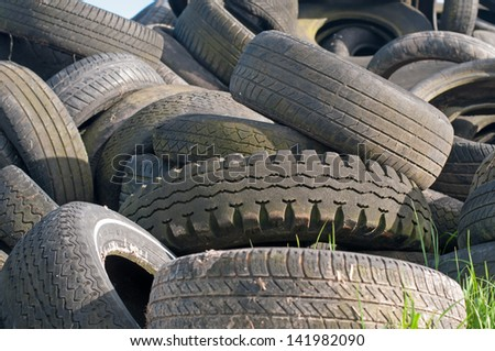 Huge pile of used tyres in different sizes - stock photo