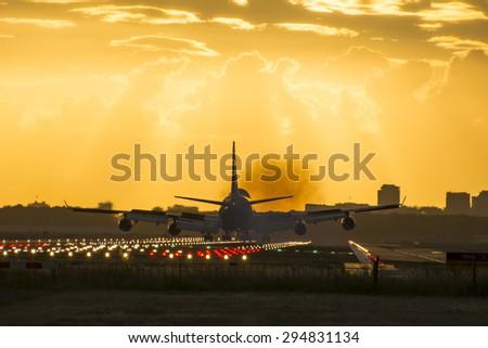 Huge plane is landing on the runway. Smoke and heat behind. - stock photo