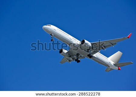 Huge plane taking off in a blue sky closeup - stock photo