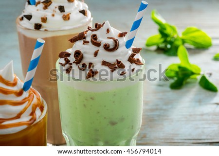Huge portion of mint milkshake decorted with chocolate chips, whipped topping and the straw. Other drinks with caramel and cocoa, leaves of mint are in the blurred background. - stock photo
