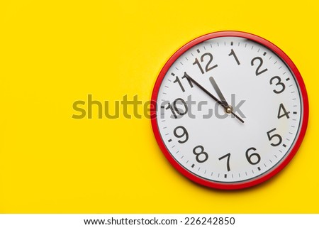 Huge red clock on yellow background. - stock photo