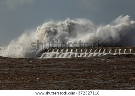 Huge sea wave crashing against a pier from Douro river mouth, northern Portugal. Detailed image. - stock photo