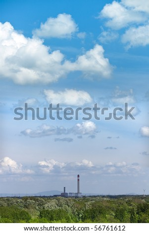 huge smokestack of a power station standing alone in natural landscape