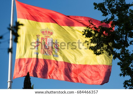 Huge Spanish flag blowing in the breeze in a square in Madrid, Spain