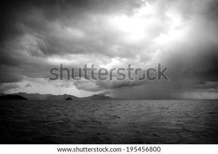Huge storm clouds with rain over a rough ocean - stock photo