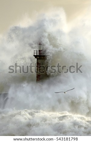 Huge stormy wave hugging violently an old lighthouse from the north of Portugal.