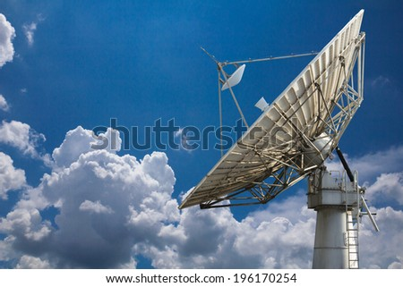 Huge television antenna disc in blue sky and many clouds  - stock photo