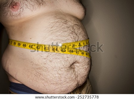 Huge waist, huge guy. has measuring tape going around a huge gut that is sagging - stock photo