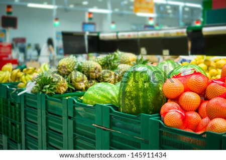 Huge watermelons, grapefruits and pineapples on boxes in supermarket