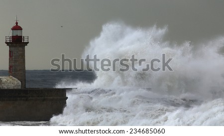 Huge wave over old lighthouse of Porto, Portugal. - stock photo
