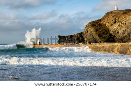 Huge waves crashing over the stone pier at Portreath harbour on the Cornwall coast - stock photo