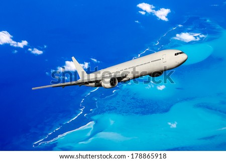 Huge white aircraft flying over the Bahamas - stock photo