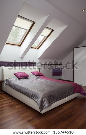 Huge white bed with silver and pink blanket - stock photo