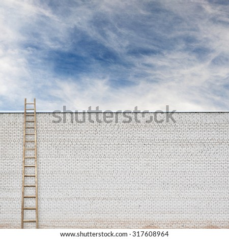 huge white brick wall with a wooden ladder and cloudy sky background - stock photo